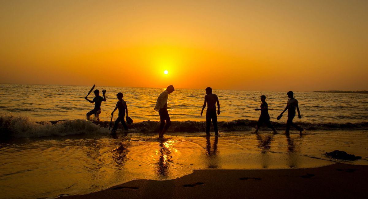 guys-enjoying-sunset-at-beach-large